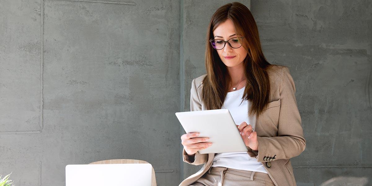 Jovem mulher de negócios a fazer a gestão de equipamentos num tablet