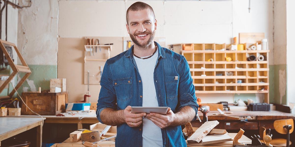 jovem empresário a sorrir enquanto utiliza um software de gestão online no tablet
